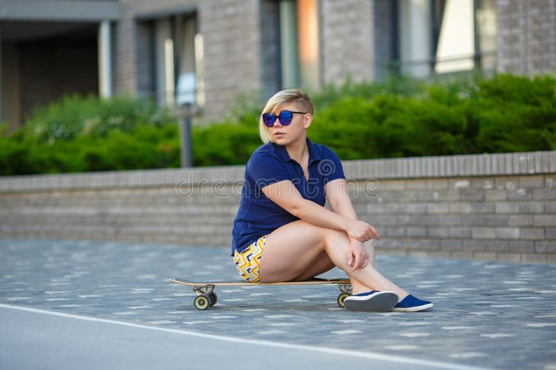 Stylish girl plus size sitting on a longboard royalty free stock images