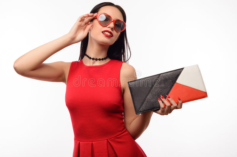 Stylish girl in red dress and clutch holds on to sunglasses in the shape of heart.  royalty free stock images