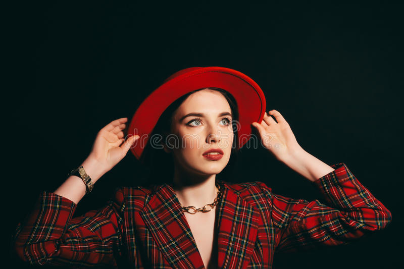 Stylish girl in red dress and hat. portrait of a young girl with long hair. Dark background stock photos