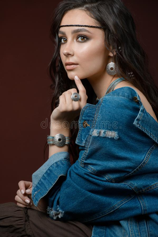 Stylish girl shows silver jewelry and accessories. Studio portrait isolated on a brown  background. The Stylish girl shows silver jewelry and accessories. Studio royalty free stock photos