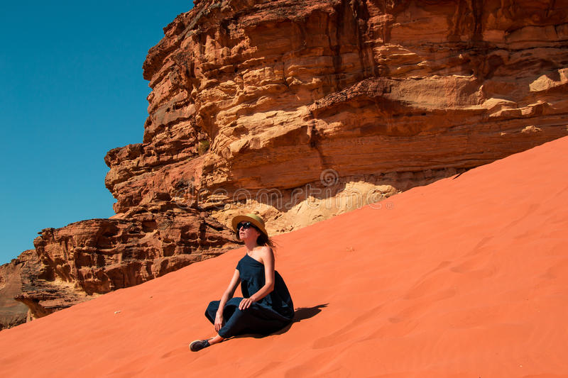 Stylish girl sitting on red dune relaxing and enjoying vacation retreat. Inspiration, travel mental health concept. Photo of the Stylish girl sitting on red dune royalty free stock photo