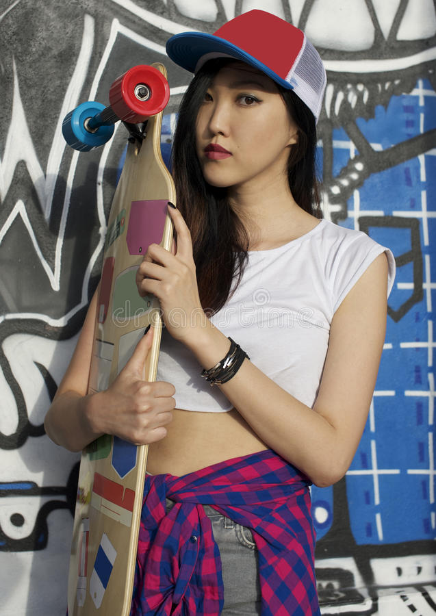 Stylish girl with skateboard. Stylish asian girl with skateboard outdoors royalty free stock images