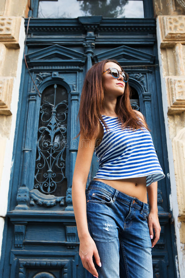 Stylish girl standing on the old door background. Girl standing on the old door background stock photos