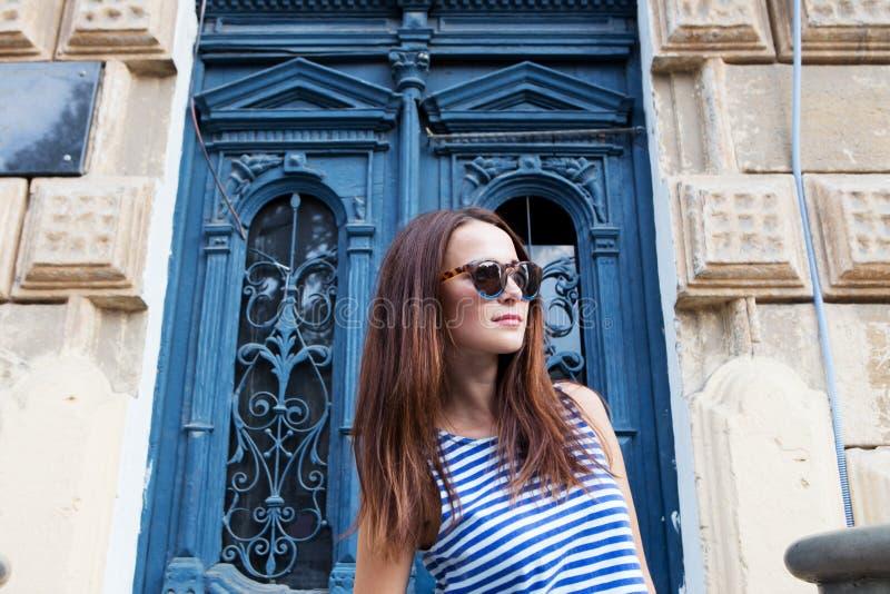 Stylish girl standing on the old door background. Girl standing on the old door background stock image
