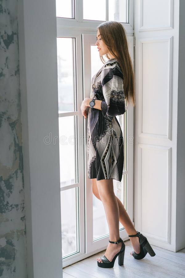 Stylish girl stands by the window in a silk dress stock photography