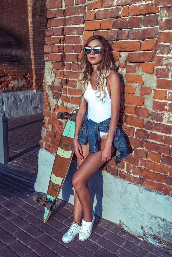 Stylish girl in summer in city, stands at brick wall anticipation of friends and girlfriends with a longboard board. Stylish girl in summer in city, stands at royalty free stock image