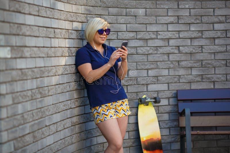 Stylish girl in sunglasses listens to headphones stock image