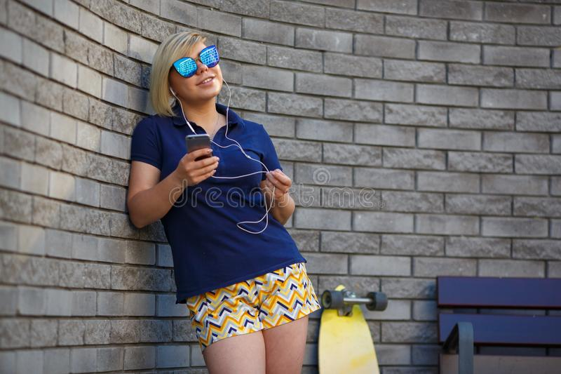 Stylish girl in sunglasses listens to headphones royalty free stock photography