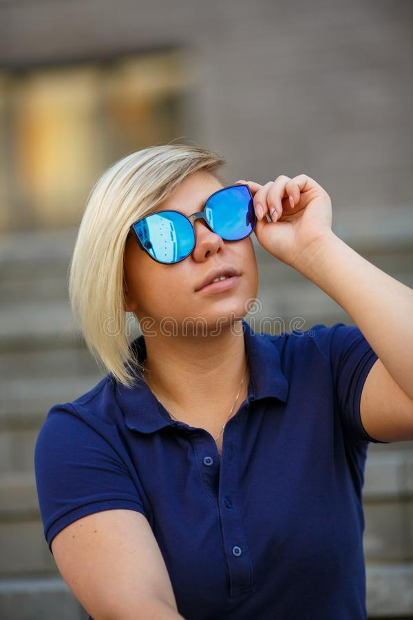 Stylish girl in sunglasses looks up to the sky stock images