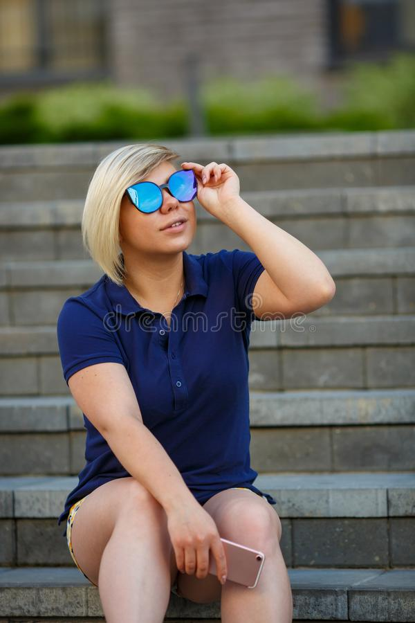 Stylish girl in sunglasses looks up to the sky stock photo