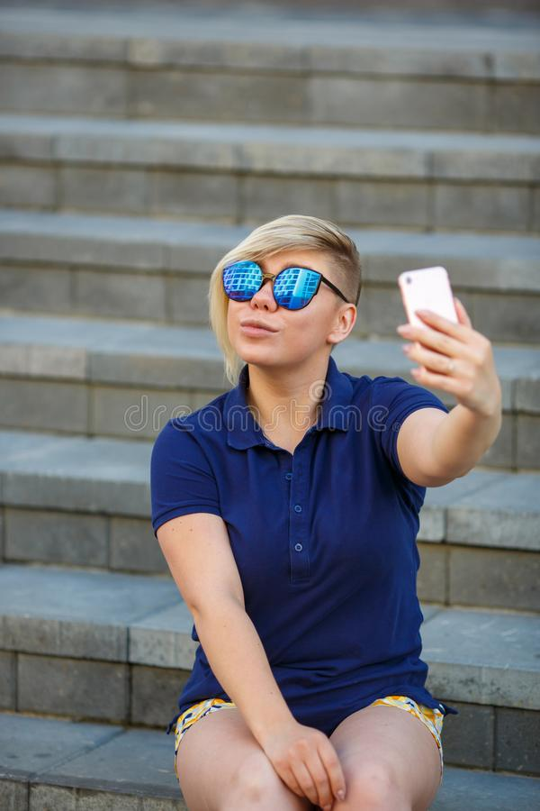 Stylish girl in sunglasses takes a selfie stock images