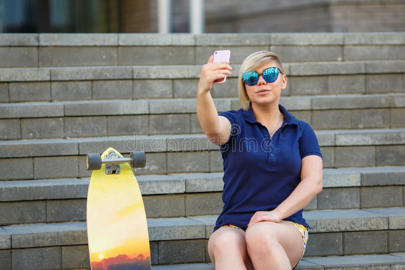 Stylish girl in sunglasses takes a selfie stock photos