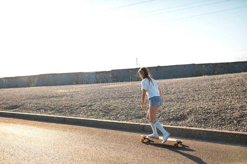 Stylish girl in white stockings ride on longboard down the street and listening music. Space for text.  stock photo
