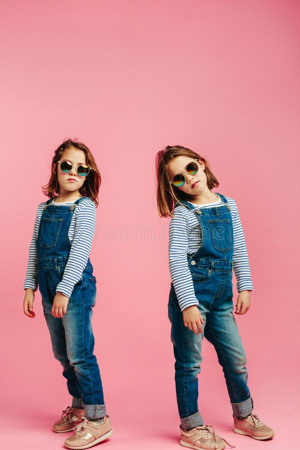 Stylish girls in denim dungarees stock images