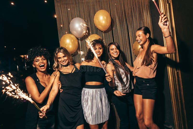 Stylish girls enjoying party at nightclub. Group of women with fireworks at party. Stylish girls enjoying party at nightclub stock image