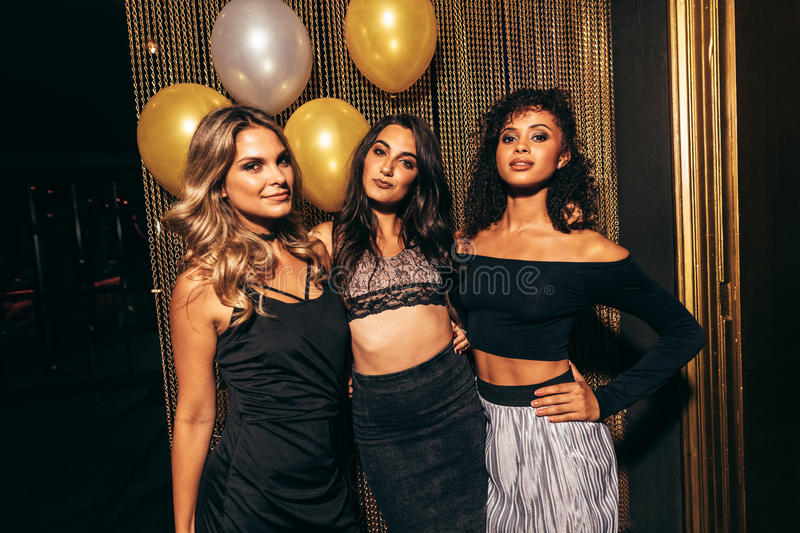 Stylish girls in the nightclub. Portrait of three stylish girls in the nightclub. Group of female friends standing together in party at pub royalty free stock images