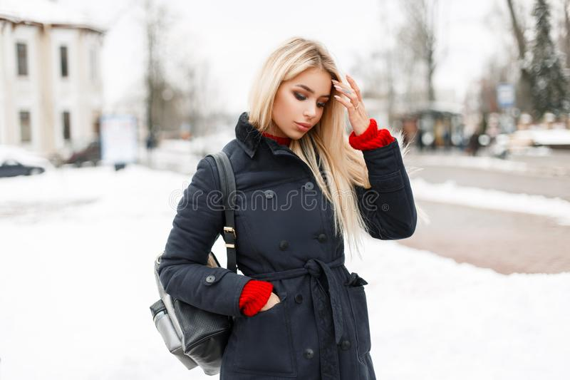Stylish glamorous young model girl in a fashion winter coat. With a bag walking in the city stock photography