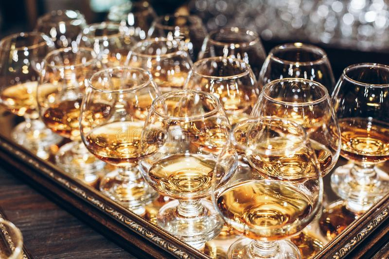 stylish glasses with cognac or whiskey on table at wedding reception. alcohol bar. tasty drinks for celebrations and events. stock photos