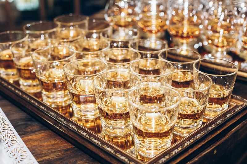 stylish glasses with cognac or whiskey on table at wedding reception. alcohol bar. tasty drinks for celebrations and events. stock image