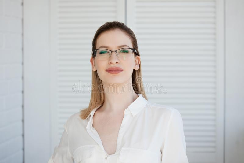 Stylish glasses in a thin frame, vision correction. Portrait of a young woman royalty free stock image