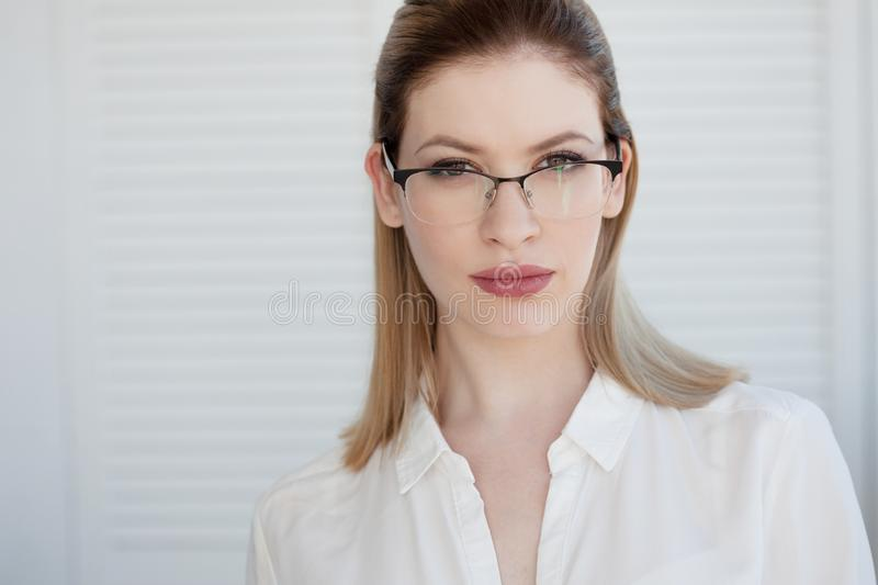 Stylish glasses in a thin frame, vision correction. Portrait of a young woman stock image