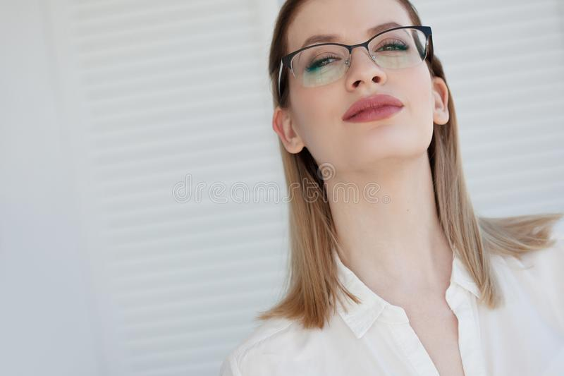 Stylish glasses in a thin frame, vision correction. Portrait of a young woman royalty free stock photography