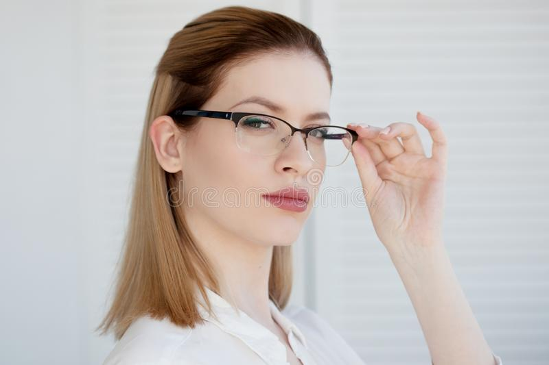 Stylish glasses in a thin frame, vision correction. Portrait of a young woman stock images