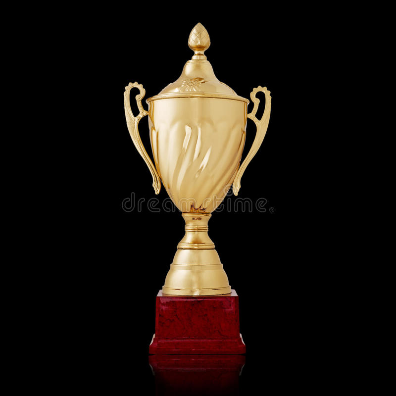 Stylish gold cup on a wooden plinth. Stylish gold cup or trophy on a wooden plinth to be awarded to the winner of a competition or championship over a black stock photo