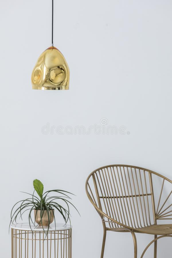 Stylish golden lap above industrial table with plant in pot on it, elegant chair next to it, real photo. With copy space stock photo