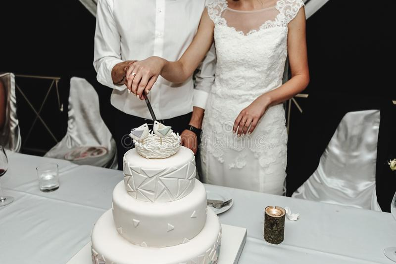 Stylish gorgeous bride and elegant groom cutting and tasting un stock photography