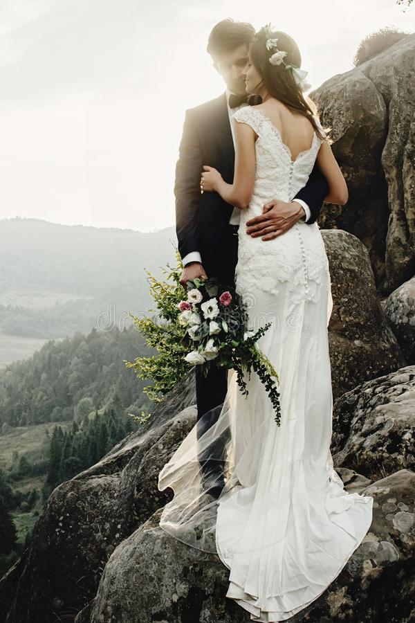 Stylish gorgeous couple newlyweds kissing on the rocks in the mountains in the evening light. Boho wedding royalty free stock images