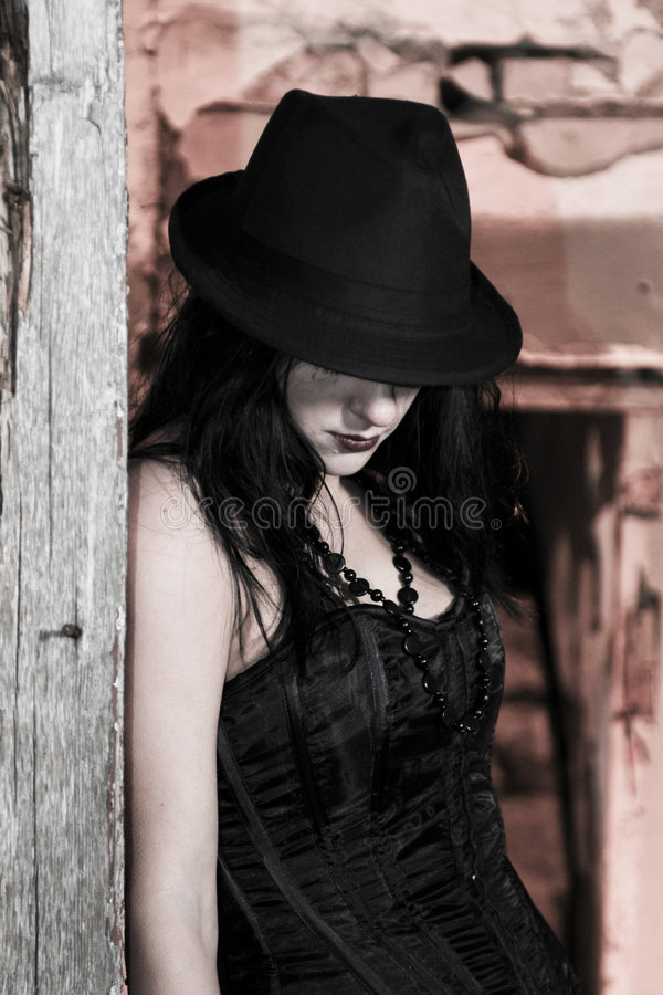 Stylish Goth Girl. A portrait of a stylish goth girl wearing a hardtop hat, standing against a ruined wall royalty free stock photography