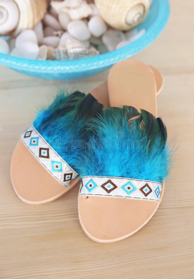 Stylish greek leather sandals with blue feathers - bohemian style stock images