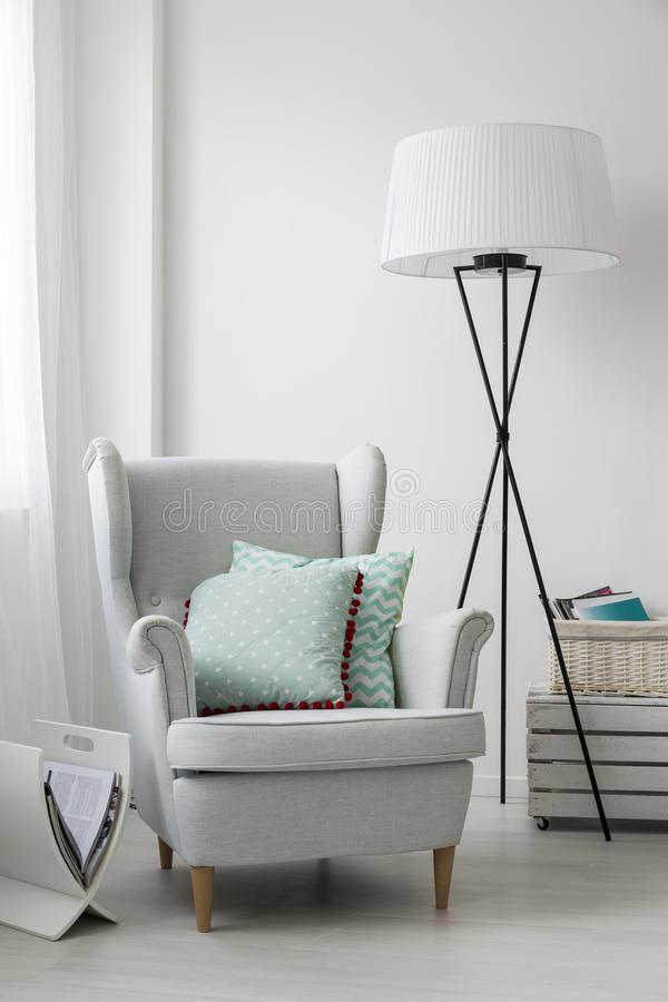 Stylish grey armchair and a floor standing lamp stock photography