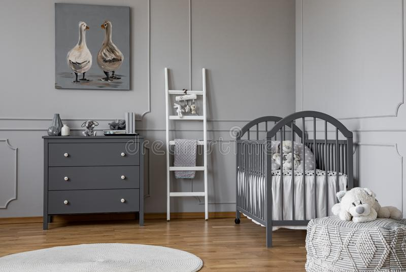 Stylish grey baby room interior with wooden furniture, white scandinavian ladder and teddy bear on pouf, real photo with copy. Space on the empty wall royalty free stock image