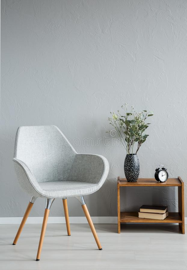 Stylish grey chair next to cabinet with vase and flowers in modern office interior, real photo. With copy space on the empty wall royalty free stock image