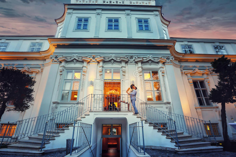 Stylish groom in blue suit and bride kissing on stairs evening b. Ackground castle Vienne Austria royalty free stock photography