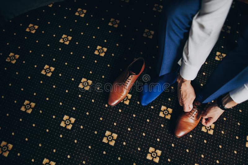 Stylish groom in blue suit putting on brown shoes near window in hotel room, top view. Morning preparation before wedding ceremony stock photo