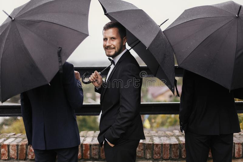 Stylish groom and groomsmen standing under black umbrella and po stock photography