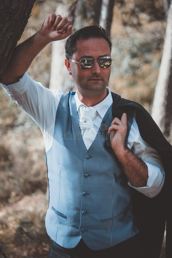 Stylish groom posing in the woods. On his wedding day royalty free stock images