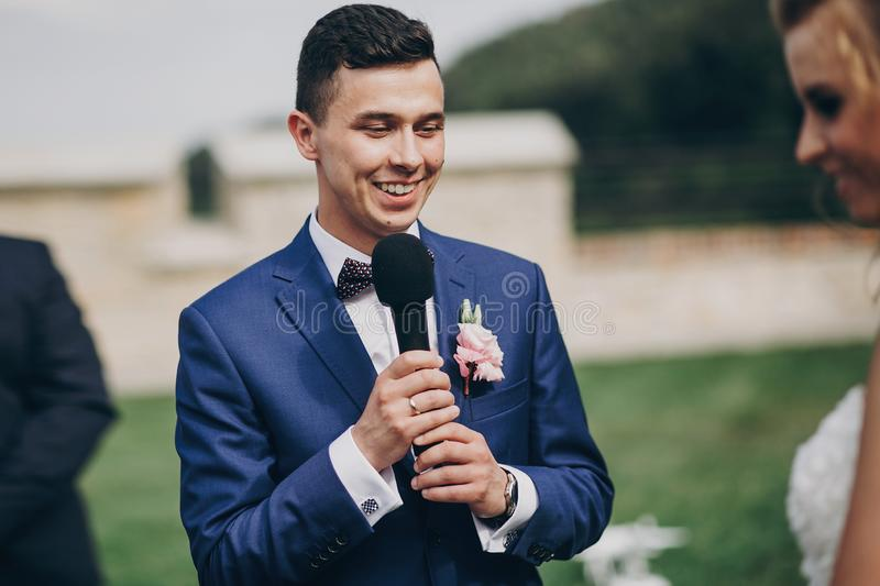 Stylish groom pronouncing vow to his beautiful bride during matrimony. Groom pronouncing speech and holding microphone. Beautiful. Wedding ceremony in summer royalty free stock image