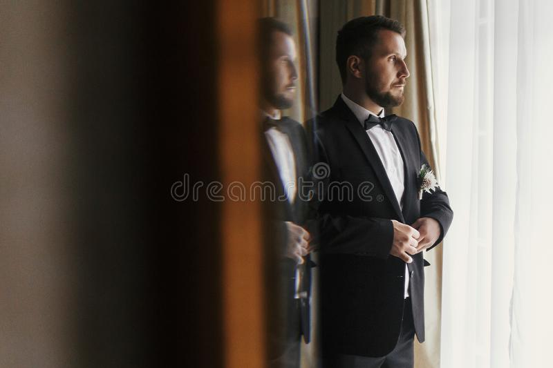 Stylish groom putting on suit and bow tie at window light. Confident and happy portrait of man. Groom getting ready in morning. C. Reative wedding photo with stock photography