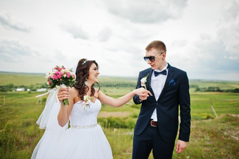 Stylish groom at sunglasses holding brides hand.  stock photography