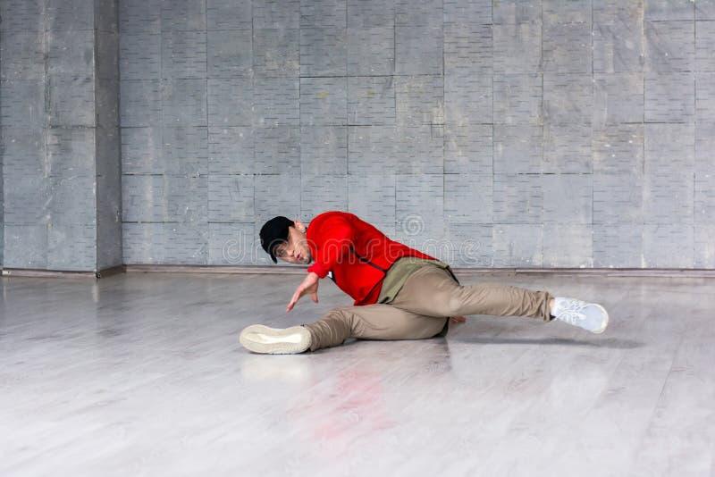 Stylish guy dancing break dance on floor. royalty free stock photography