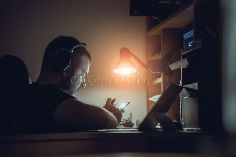 Stylish guy works at the computer in the office at night royalty free stock image