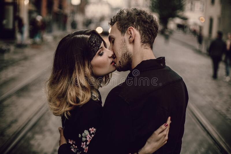 stylish gypsy couple in love kissing hugging in evening city street. woman and man gently embracing, romantic french atmospheric royalty free stock photos