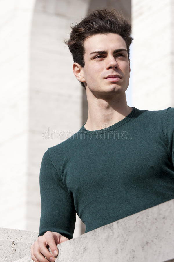Stylish hair young man outdoors on the ledge, tight knit. A beautiful young European (Italian) man is outdoors resting on the ledge. He is located in a park in stock image