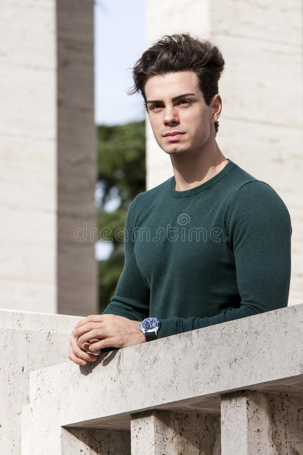 Stylish hair young man outdoors on the ledge, tight knit. A beautiful young European (Italian) man is outdoors resting on the ledge. He is located in a park in royalty free stock photo