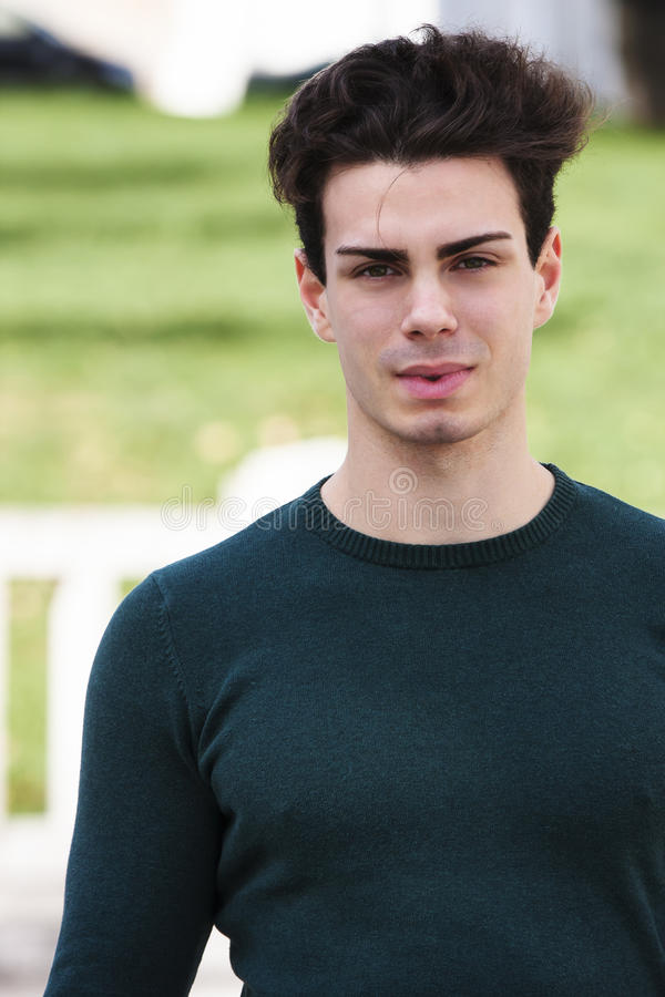 Stylish hair young man outdoors, tight knit. A beautiful young European (Italian) man is outdoors. He is located in a park in Rome. The boy wears a tight knit royalty free stock photography