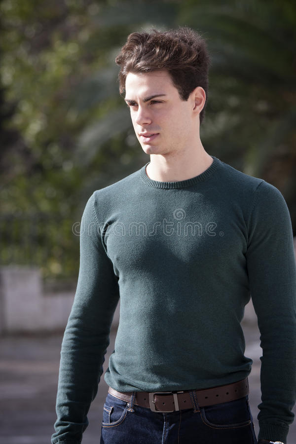 Stylish hair young man outdoors, tight knit intense light. A beautiful young European (Italian) man is outdoors. He is located in a park in Rome. The boy wears a stock photo